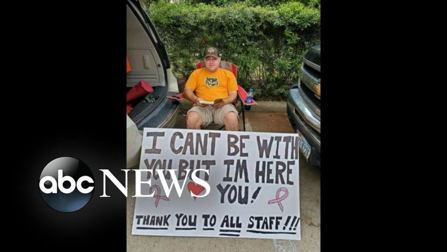 Man holds sign outside hospital as wife receives chemotherapy – ABC News